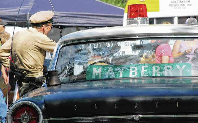Todd Beckett of Massillon portrays television character Barney Fife during the Mechanicsburg Summer Celebration in Goshen Memorial Park. Beckett was posing with his patrol car that is an iconic set of wheels inspired by The Andy Griffith Show.
