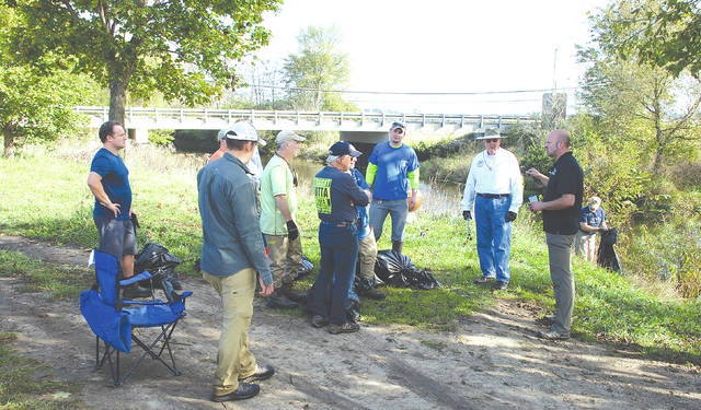 Ron Lewis, president of the Trout Unlimited Madmen chapter, organizes his volunteers for a systematic cleanup of the Mad River on Saturday.